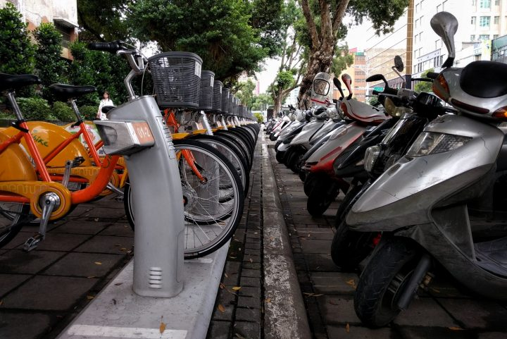 A YouBike station mirrors the scooter parking row